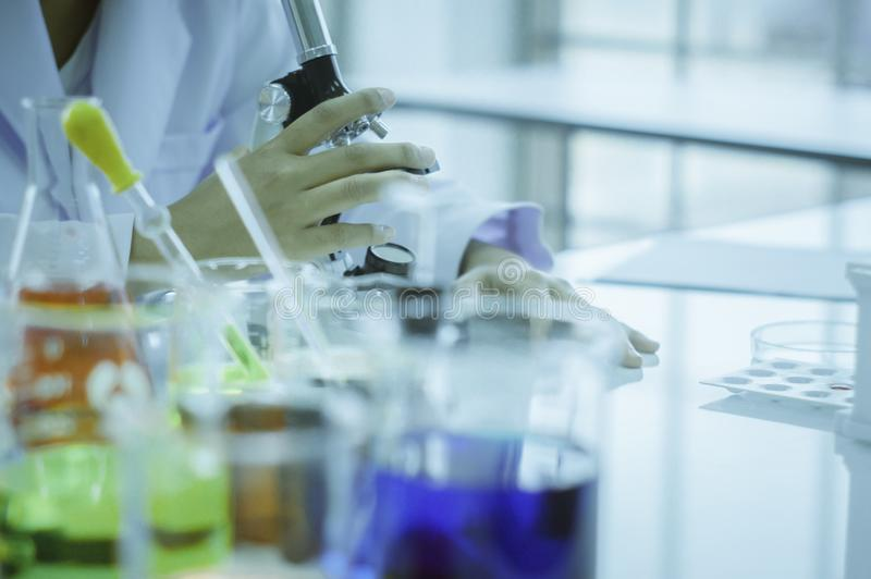 Chemist, microscope, chemical testing in lab, concept for improving safety products before applying to consumers stock images