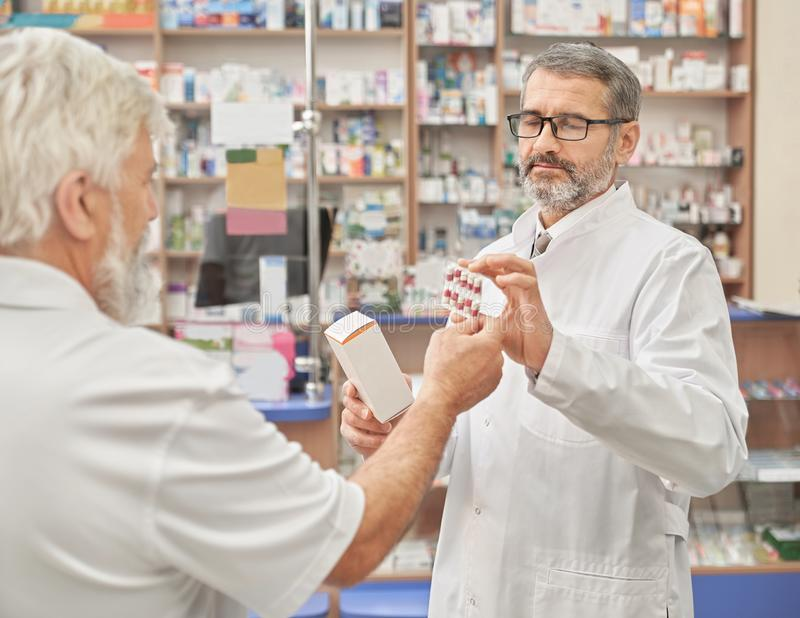 Chemist offering medicaments to old customer in pharmacy. Pharmacist holding blaster pack of pills and medical box. Professional specialist helping pensioner to royalty free stock images