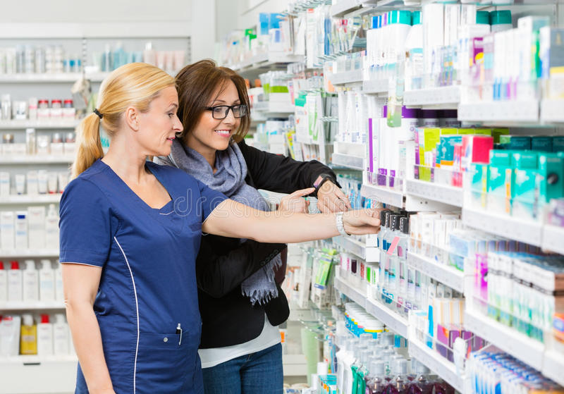Chemist Removing Product For Customer Showing. Mature female chemist removing product for customer showing smartwatch in pharmacy royalty free stock photo