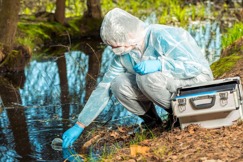 Chemist researcher ecologist produces water. From a forest lake stock images