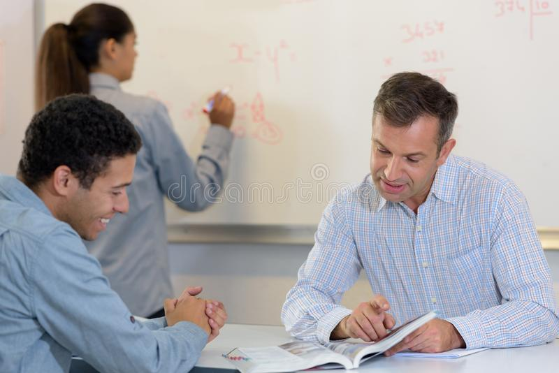 Chemist student writing equations on white board stock photography