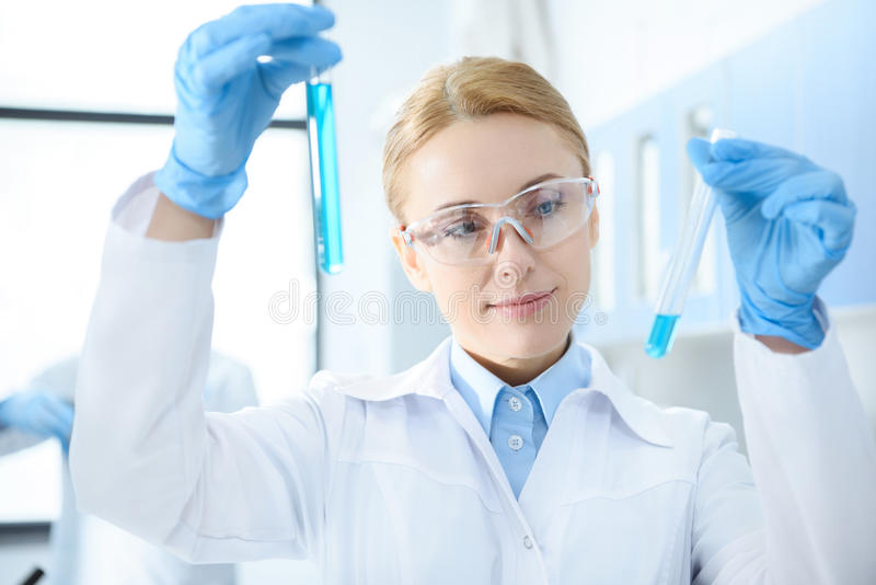 Chemist in white coat holding test tubes with reagents and making experiment. Smiling chemist in white coat holding test tubes with reagents and making royalty free stock photography