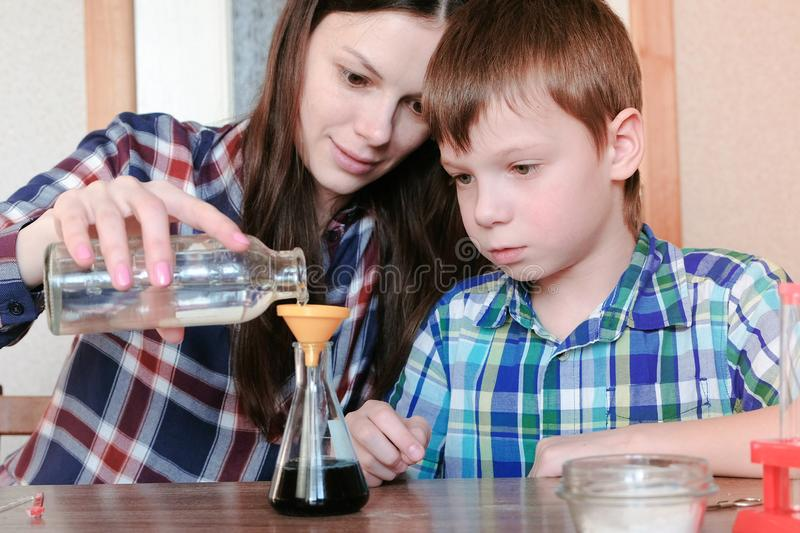 Chemistry experiments at home. Woman pouring the water into the flask from bottle using funnel. stock image