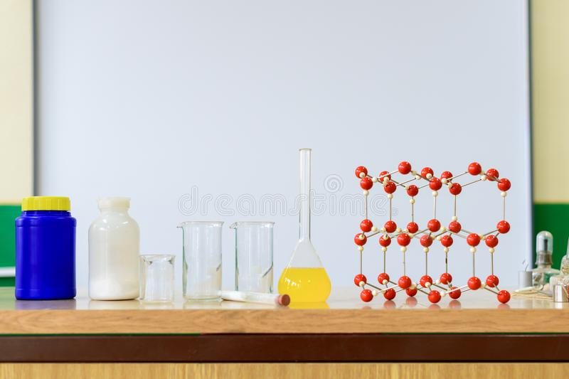 Chemistry glassware with liquid formula and molecular structure model at the science classroom. Chemistry glassware with liquid formula and molecular structure stock photo
