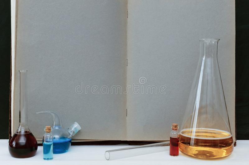 Chemistry handbook with blank pages sheet and colorful flasks and vials on school blackboard background. royalty free stock photos