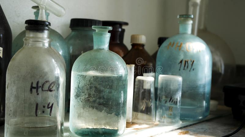 Chemistry laboratory with acid solutions in old glass flasks. Close up for the table with chemical solutions in the lab royalty free stock images