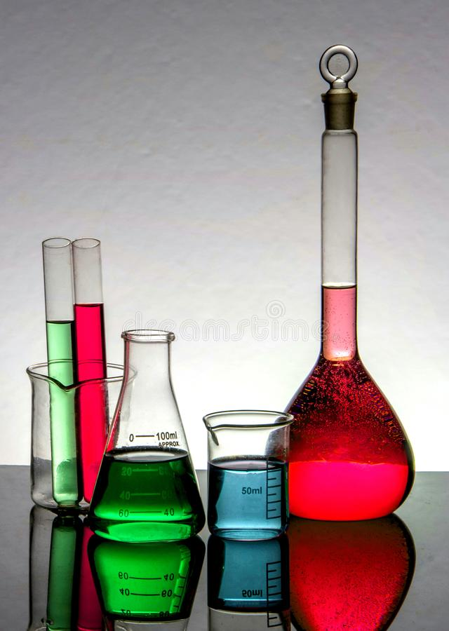 Chemistry laboratory beakers ,and test tubes on a reflecting surface and periodic table background stock image