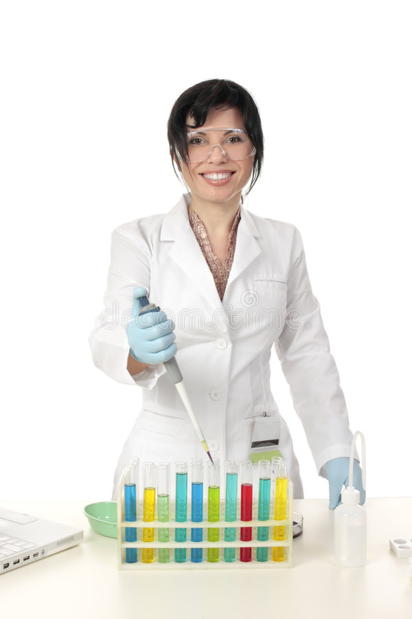 Chemistry, science, testing. Smiling female laboratory worker standing in front of test tubes with a pipette in hand royalty free stock image