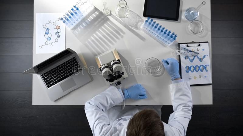 Chemistry student doing scientific experiments, conducting lab research, topview stock photo