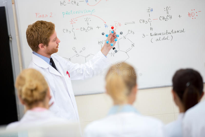 Chemistry teacher hold molecular model and teach students in classroom. Young male chemistry teacher show molecular model to students in classroom royalty free stock image