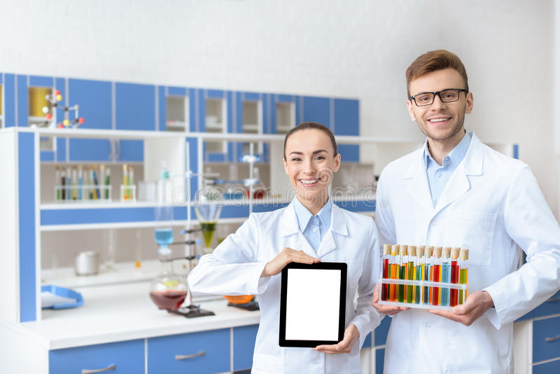 Chemists in lab coats holding digital tablet and test tubes. Young smiling chemists in lab coats holding digital tablet and test tubes stock images