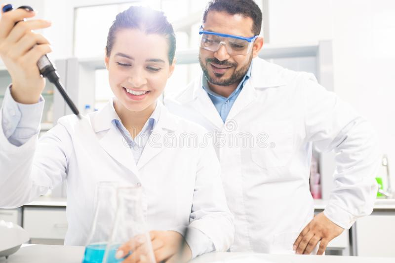 Chemists performing experiment in laboratory royalty free stock photo
