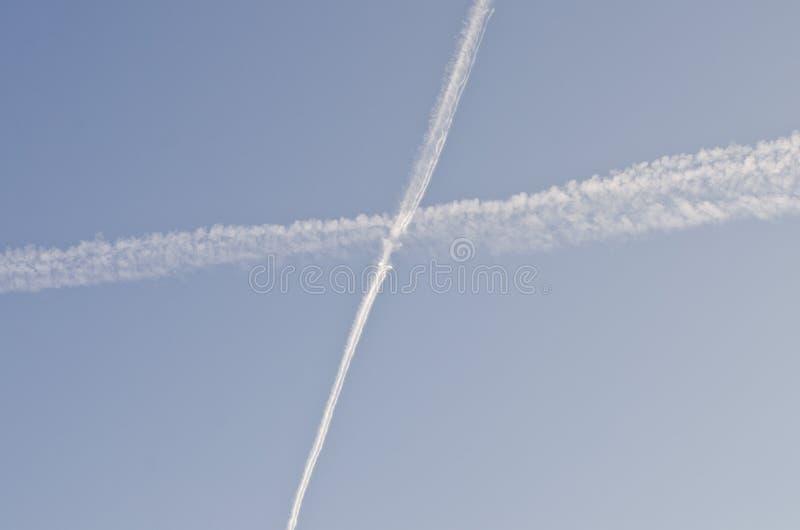 Chemtrails w niebie krzyżuje each inny obrazy stock
