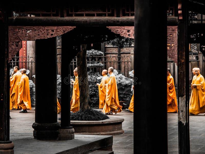 CHENGDU, CHINA - 27. AUGUST 2012: Buddhistische Mönche in den orange Roben geht zwischen Spalten von Wenshu-Kloster in Chengdu lizenzfreie stockfotos