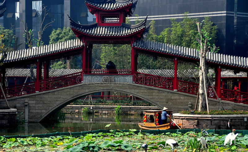 Chengdu, China: Covered Bridge and Boat at Long Tan Water Town. Woman poles a wooden boat under a traditional covered Chinese bridge at Long Tan Water Town in stock photos