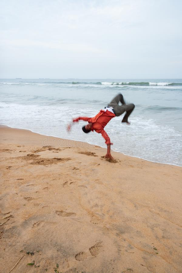 Aman performs a somersault near the breaking waves of the rough. Chennai, India - September 6, 2007: Aman performs a somersault near the breaking waves of the stock photography