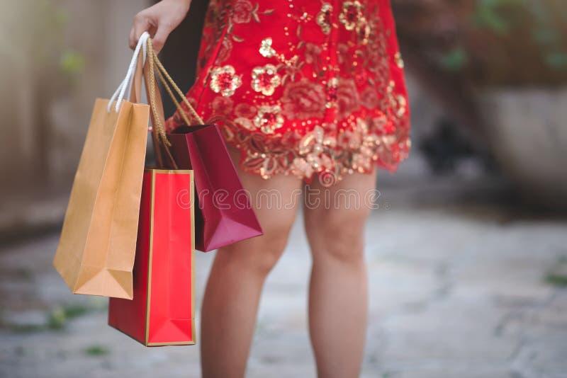 Cheongsam传统红色礼服藏品购物带来的亚裔中国妇女在农历新年节日 库存图片