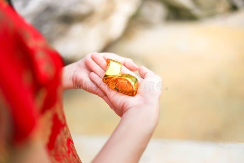 Cheongsam asiático bonito do desgaste de mulher e guardar barras de ouro como presentes pelo ano novo chinês para você Ano novo c imagens de stock royalty free