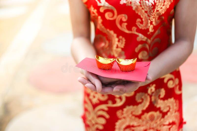 Cheongsam asiático bonito do desgaste de mulher e guardar barras de ouro como presentes pelo ano novo chinês para você Ano novo c foto de stock