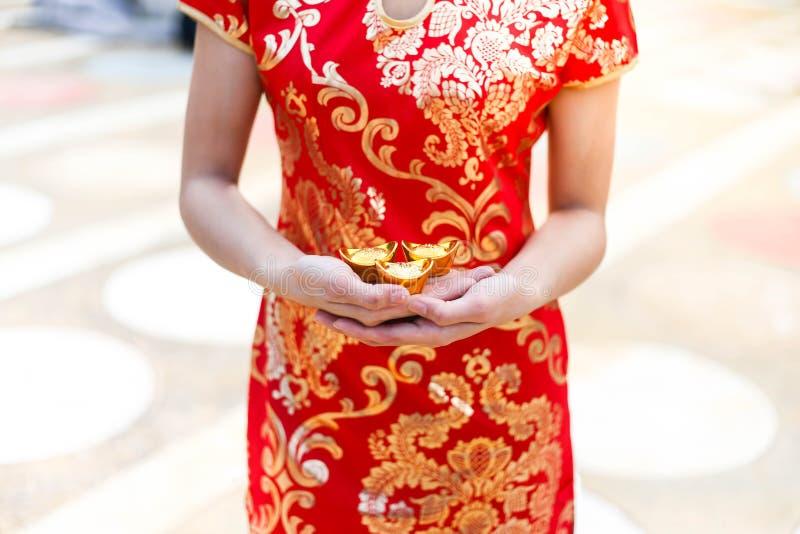 Cheongsam asiático bonito do desgaste de mulher e guardar barras de ouro como presentes pelo ano novo chinês para você Ano novo c fotografia de stock