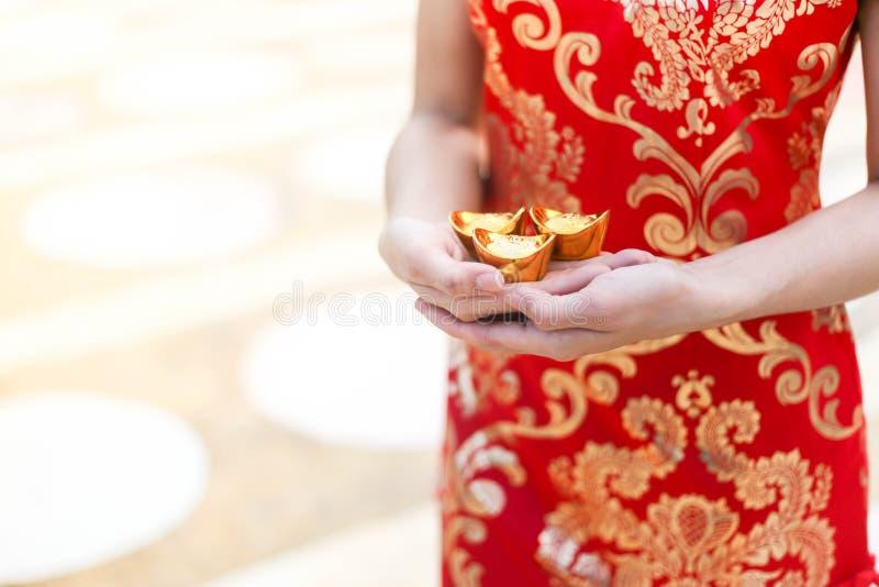 Cheongsam asiático bonito do desgaste de mulher e guardar barras de ouro como presentes pelo ano novo chinês para você Ano novo c fotografia de stock royalty free