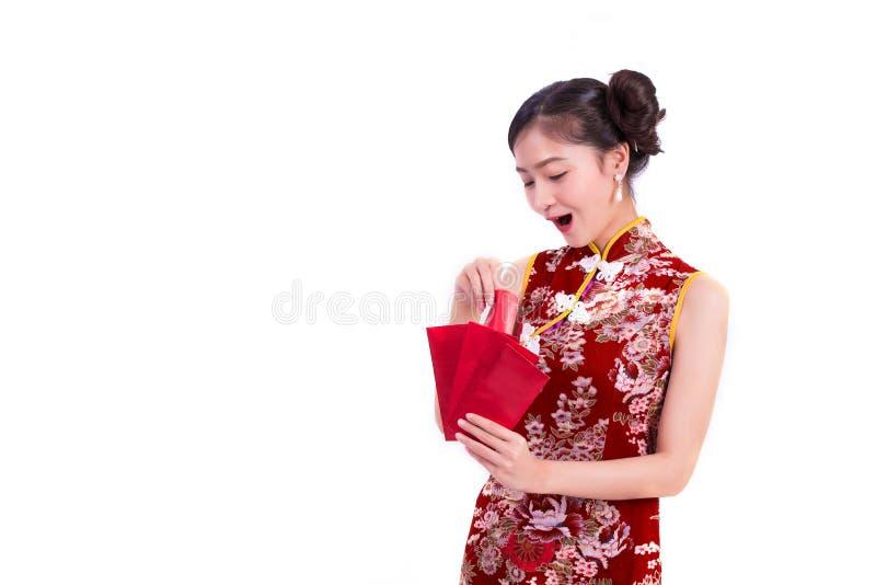 Cheongsam da mulher asiática nova da beleza e pacote vestindo guardar de dinheiros e de gesto surpreendente no evento chinês do f foto de stock royalty free