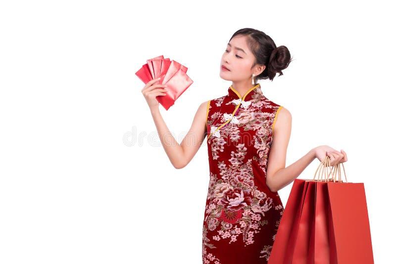 Cheongsam da mulher asiática nova da beleza e salvar como o gesto do milionário no evento chinês do festival do ano novo dinheiro fotos de stock
