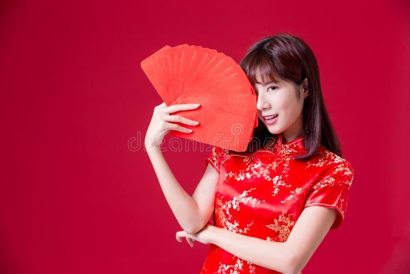 Cheongsam del desgaste de mujer y sobre rojo de la demostración en Año Nuevo chino imagen de archivo libre de regalías
