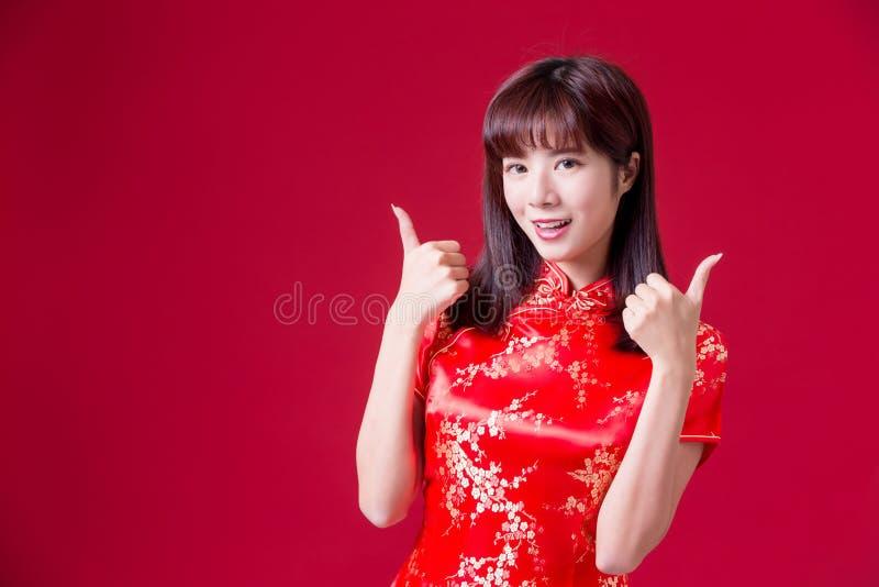 cheongsam för kvinnakläder och showtumme upp i kinesiskt nytt år royaltyfri foto