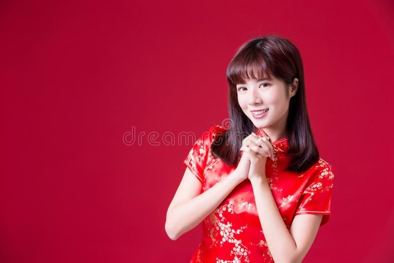cheongsam och leende för kvinnakläder till dig i kinesiskt nytt år fotografering för bildbyråer