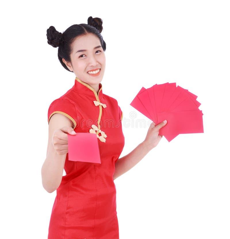 Cheongsam ou qipao vestindo da mulher que dão envelopes vermelhos no conceito foto de stock