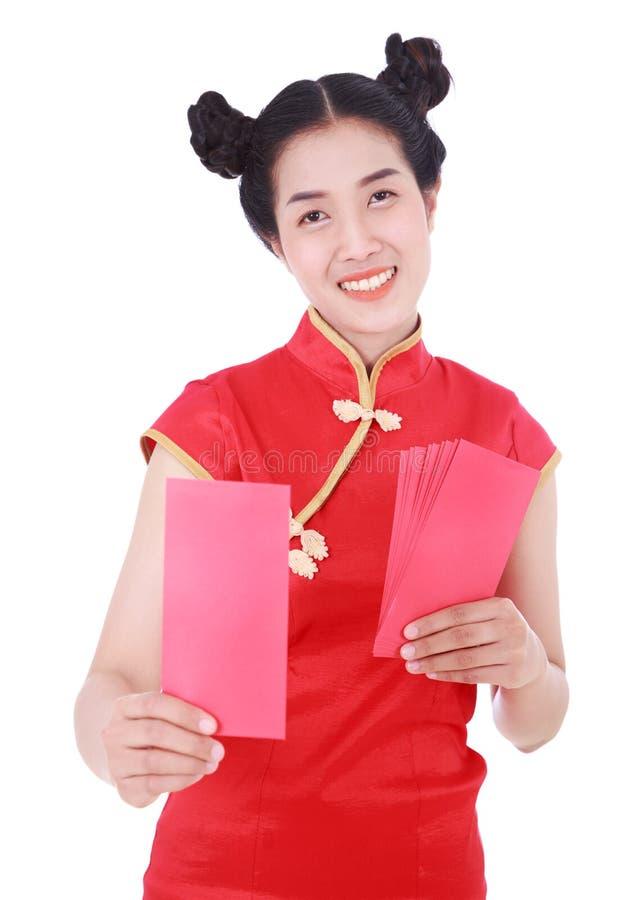 Cheongsam ou qipao vestindo da mulher que dão envelopes vermelhos no conceito imagem de stock