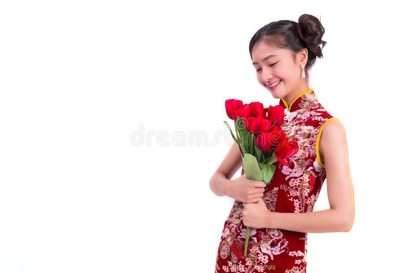 Cheongsam vestindo da mulher asiática nova da beleza e guardar a rosa do vermelho imagens de stock