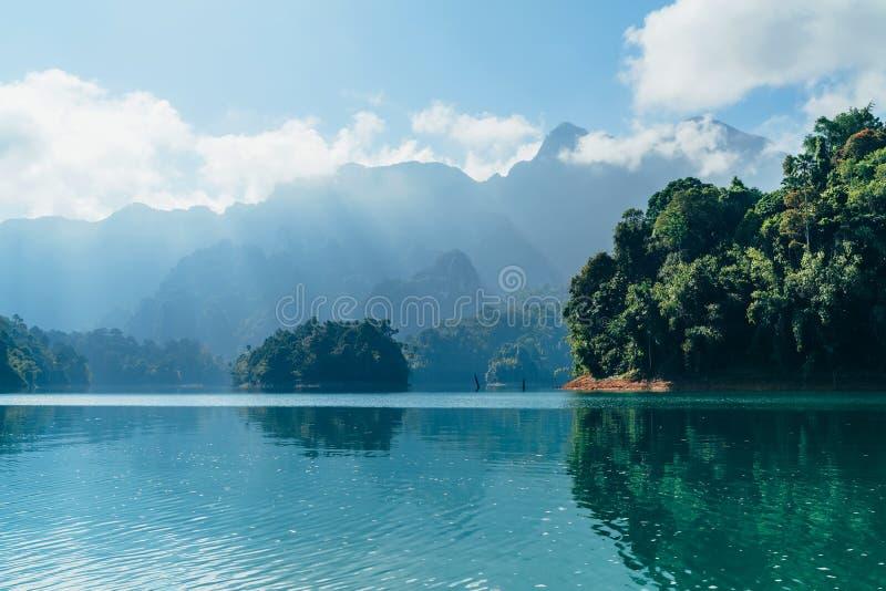 Cheow有雨林密林的Lan湖难以置信的看法有发光通过白色云彩的太阳光芒的银行的 Surat Thani 免版税库存照片