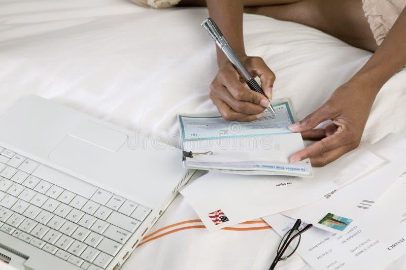Cheque de la escritura de la mujer en cama por la computadora portátil fotos de archivo libres de regalías