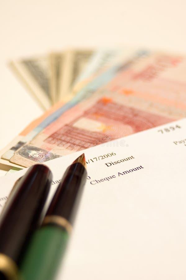 Cheque, dinero, pluma foto de archivo