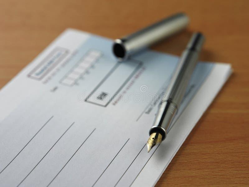 Cheque y pluma fotos de archivo libres de regalías