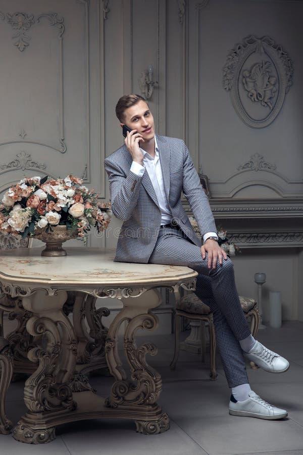 Cher jeune homme avec une coupe de cheveux dans un costume, se reposant à une table dans une chambre avec un intérieur classique  photos stock