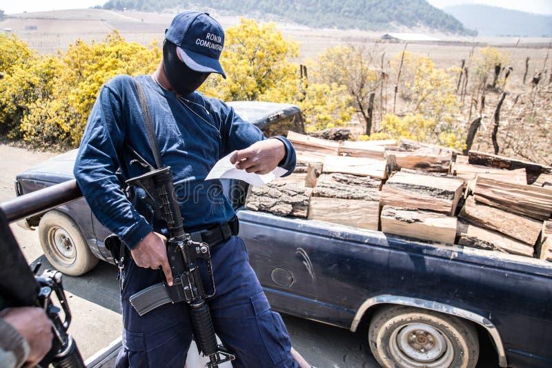 Cheran : le membre de la force de sécurité volontaire vérifie une autorisation de collection de bois de chauffage image stock