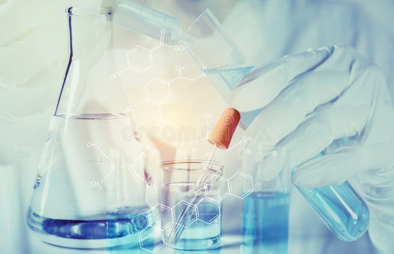 Chercheur avec les tubes à essai chimiques de laboratoire en verre avec le liquide pour la recherche analytique, médicale, pharma image libre de droits