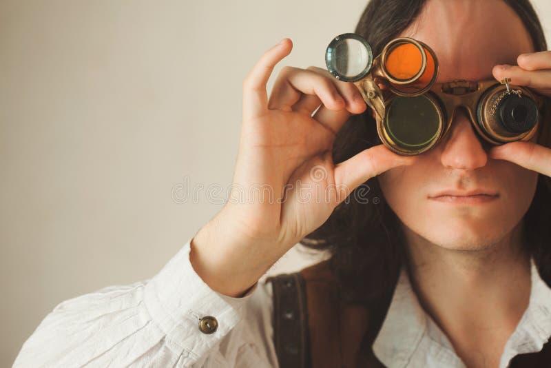 Chercheur de style de Steampunk mécaniste du monocle avec un grand nombre de lentilles regardant quelque chose photos libres de droits