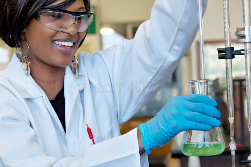 Chercheur féminin heureux dans le laboratoire chimique photos stock