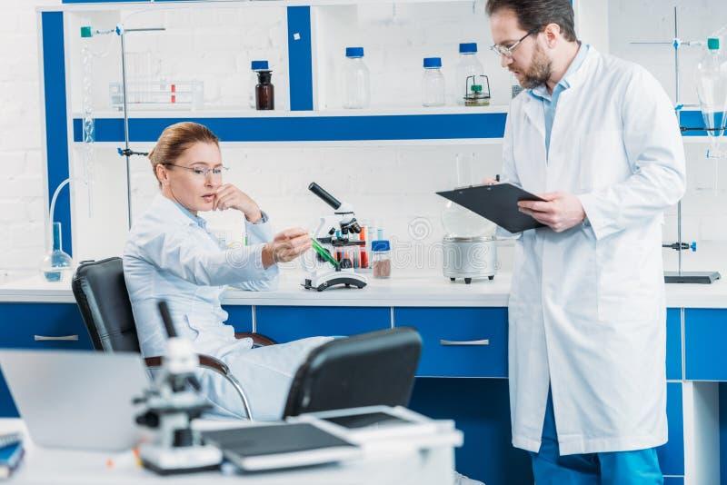 chercheur scientifique regardant le flacon avec du réactif à disposition avec le collègue près image libre de droits