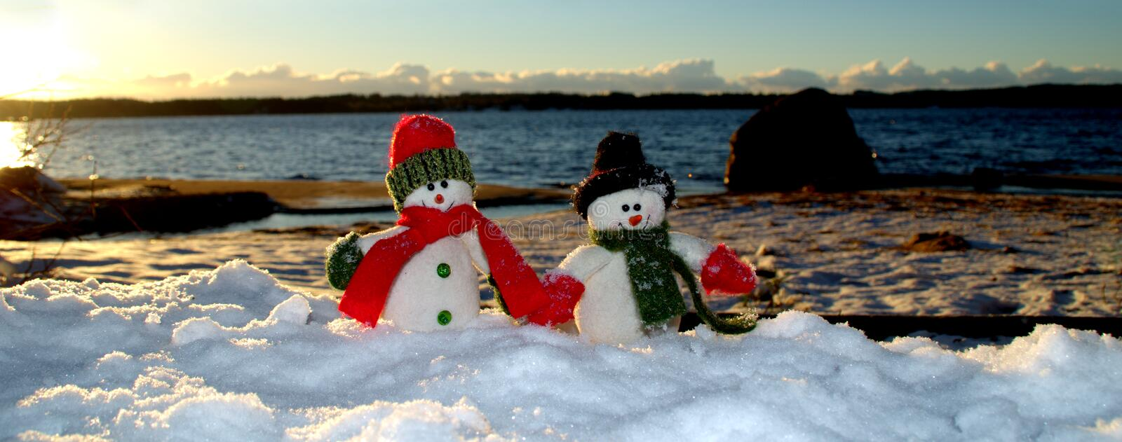 Cherful snowmans walking along the beach in the snow. Two happy snowmans on the beach in snow, bottom part of picture can be used for text. It could be a man and stock photo