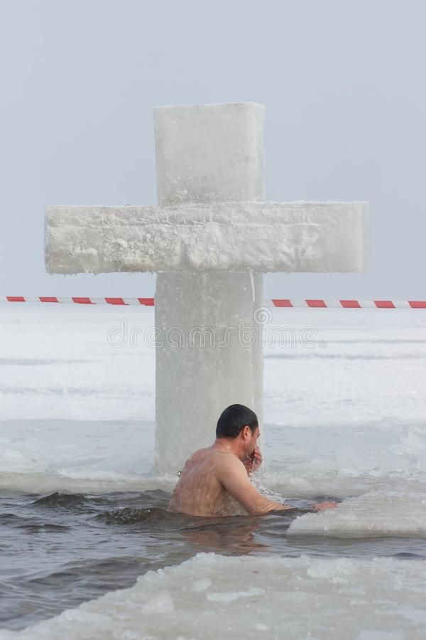 CHERKASSY, UKRAINE - January 19, 2017: Traditional ice swimming in Orthodox church Holy Epiphany Day. Ice cross and Ice-hole for bathing into sub-zero water on royalty free stock photography