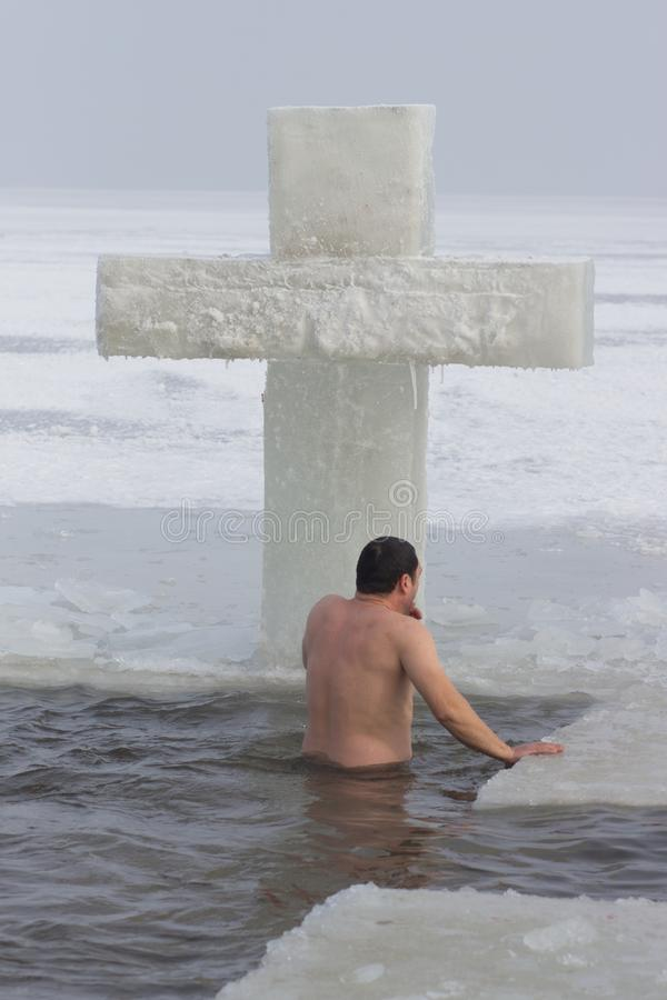 CHERKASSY, UKRAINE - January 19, 2017: Traditional ice swimming in Orthodox church Holy Epiphany Day. Ice cross and Ice-hole for bathing into sub-zero water on stock image