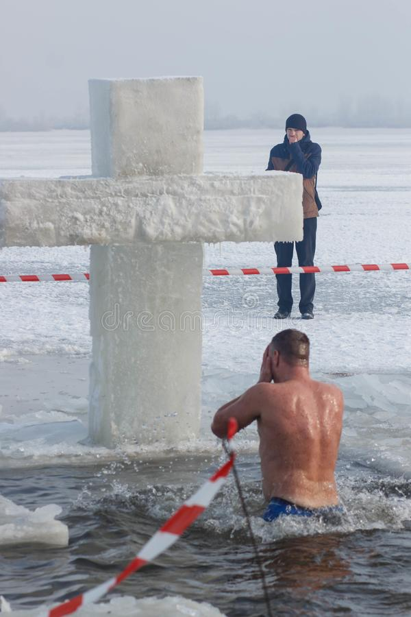 CHERKASSY, UKRAINE - January 19, 2017: Traditional ice swimming in Orthodox church Holy Epiphany Day. Ice cross and Ice-hole for bathing into sub-zero water on stock photo
