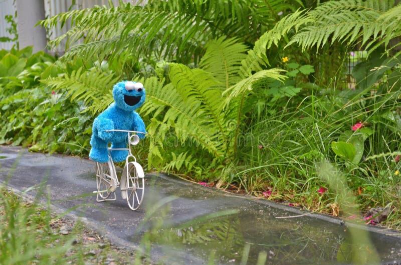 Cherkasy, de Oekraïne, 13 Juni, 2019 - Toy Cookie-grappig monster berijdend een witte fiets op natte weg onder groene installatie stock afbeelding