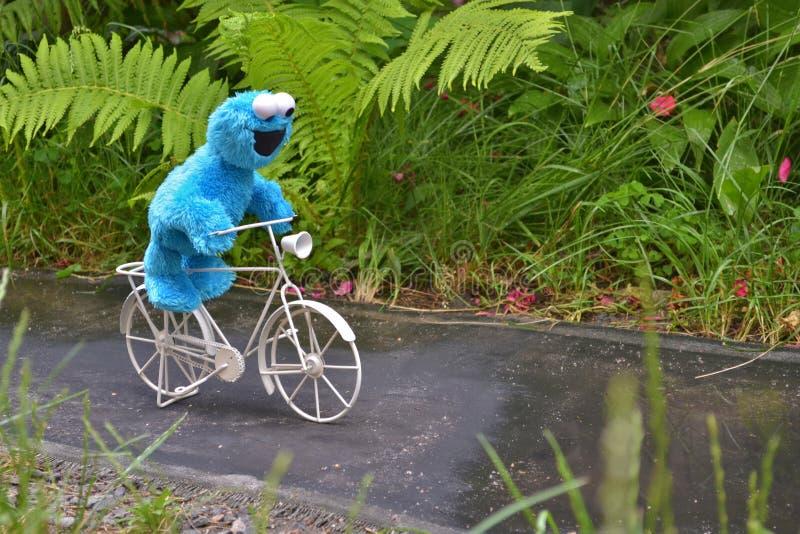 Cherkasy, Ucrânia, o 13 de junho de 2019 - equitação engraçada do monstro de Toy Cookie uma bicicleta branca no trajeto entre as  imagem de stock royalty free