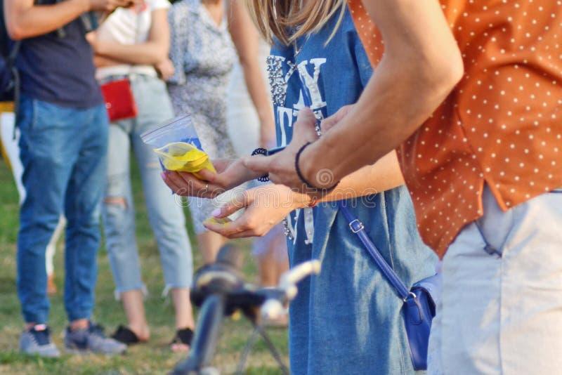 Cherkasy, Ucrania, el 24 de agosto de 2018 - el banquete del Holi en el parque, mamá da a su hija Holi la pintura imagen de archivo libre de regalías